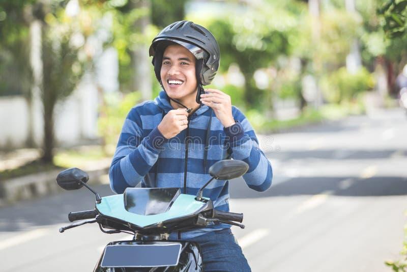 Mann, der seinen Motorradsturzhelm befestigt stockfotos