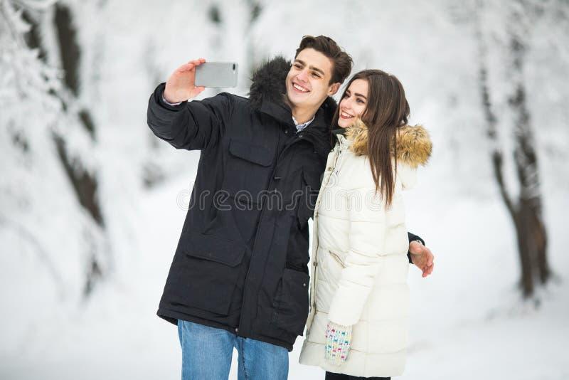 Mann, der Selfie-Foto jungen romantischen Paar-Lächeln-Schnee Forest Outdoor Winter Pine Woods nimmt Paare machen selfie lizenzfreies stockbild
