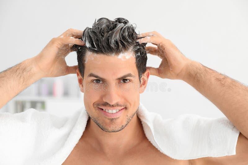 Mann, der Shampoo auf sein Haar anwendet lizenzfreie stockfotografie
