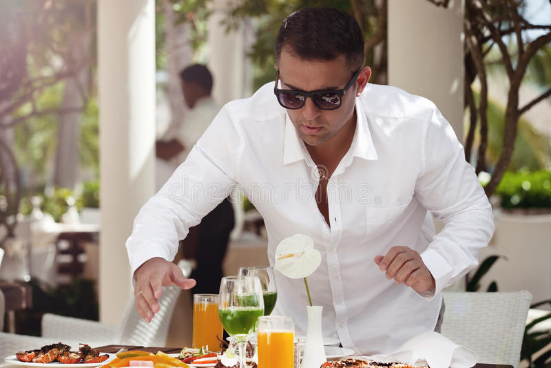 Mann, der sich draußen in einem Luxusrestaurant entspannt stockbild