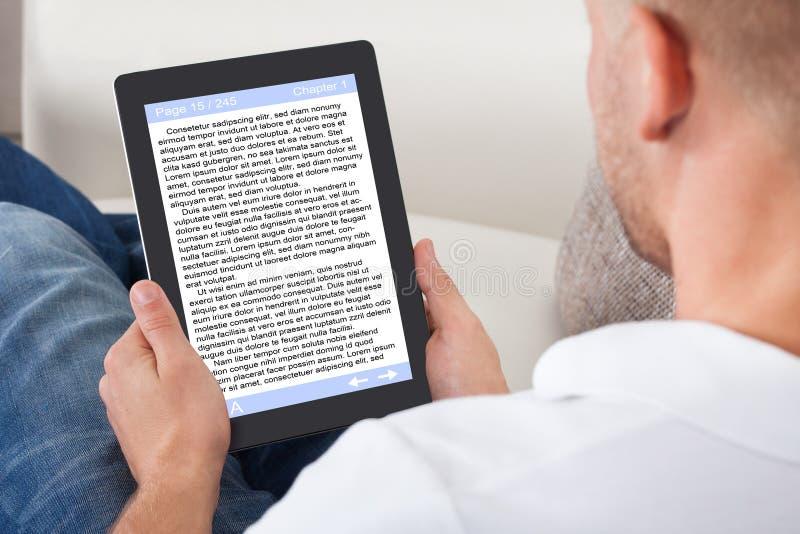 Mann, der sich zu Hause entspannt, ein eBook online lesend stockfoto