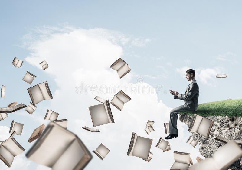 Mann, der smarphone verwenden und viele Bücher, die in einer Luft fliegen lizenzfreie stockfotos