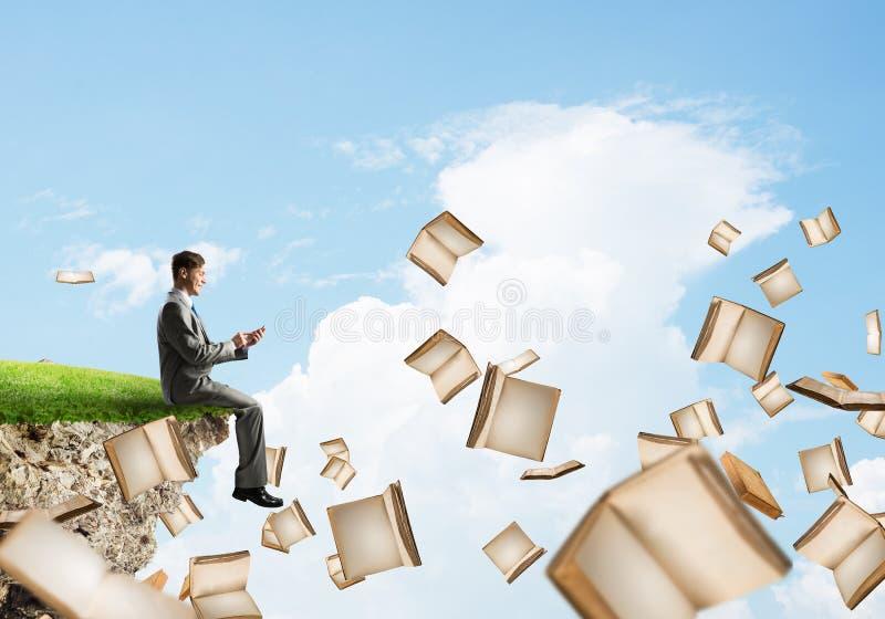 Mann, der smarphone verwenden und viele Bücher, die in einer Luft fliegen stockbild