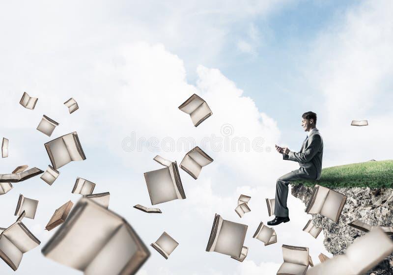 Mann, der smarphone verwenden und viele Bücher, die in einer Luft fliegen lizenzfreie stockbilder
