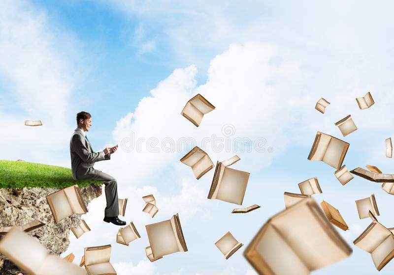 Mann, der smarphone verwenden und viele Bücher, die in einer Luft fliegen lizenzfreies stockfoto