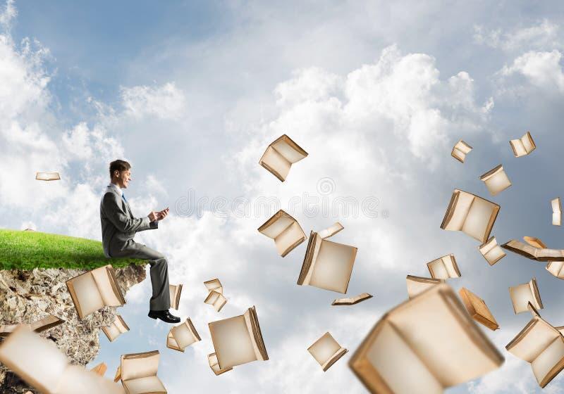 Mann, der smarphone verwenden und viele Bücher, die in einer Luft fliegen stockfoto