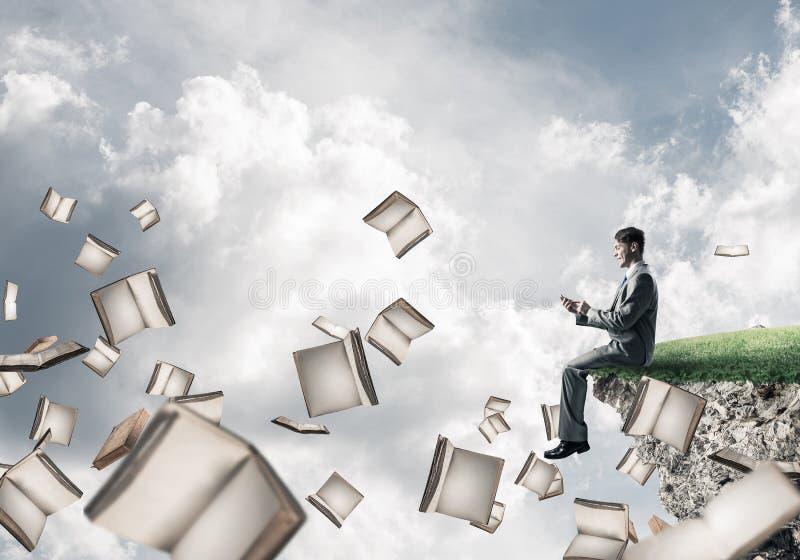 Mann, der smarphone verwenden und viele Bücher, die in einer Luft fliegen lizenzfreies stockbild