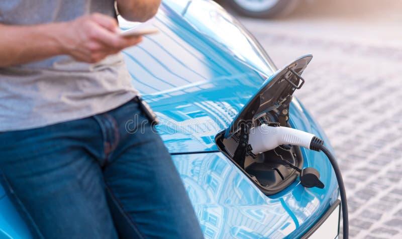 Mann, der Smartphone bei der Aufladung des Autos hält lizenzfreies stockfoto
