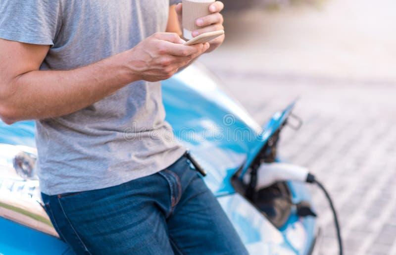 Mann, der Smartphone bei der Aufladung des Autos verwendet lizenzfreies stockbild