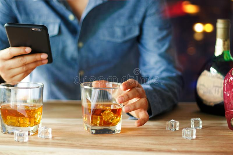 Mann, der Smartphone beim Trinken von Whiskyalkoholgetränk a verwendet lizenzfreies stockfoto