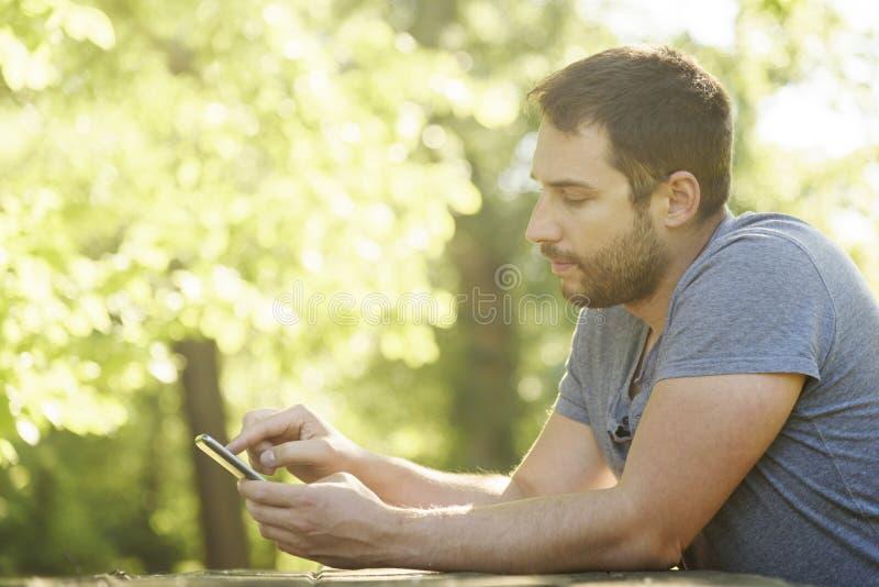Mann, der Smartphone in der Natur verwendet lizenzfreie stockbilder