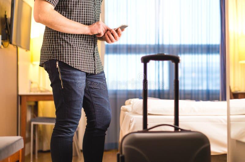 Mann, der Smartphone im Hotelzimmer mit Gepäck und Koffer verwendet stockbilder