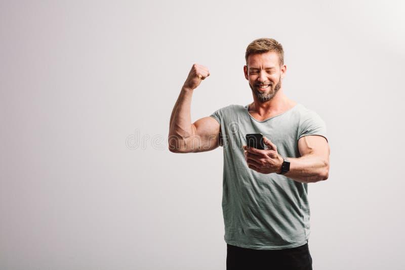 Mann, der Smartphone mit gewinnender Geste betrachtet stockfoto