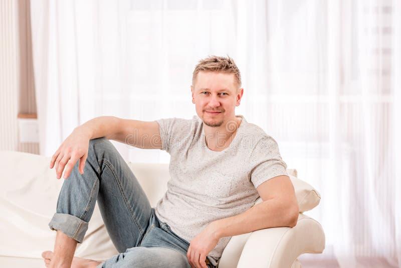 Mann, der am Sofa im Schlafzimmer sitzt lizenzfreie stockbilder