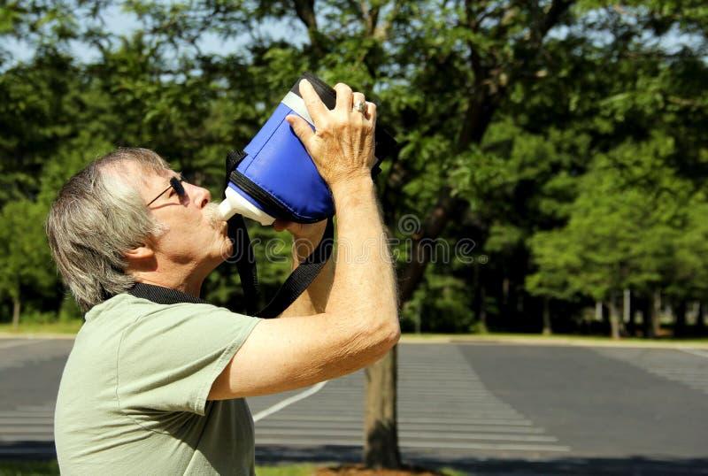 Mann in der Sonne nimmt ein Getränk zum Hydrat stockbilder
