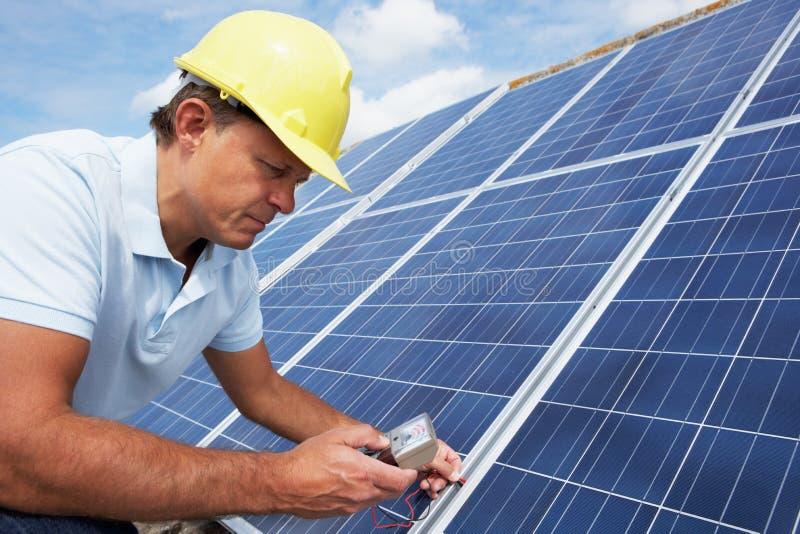 Mann, der Sonnenkollektoren installiert stockfotografie