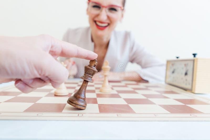 Mann, der Spiel des Schachs gegen Geschäftsfrau löst lizenzfreies stockfoto
