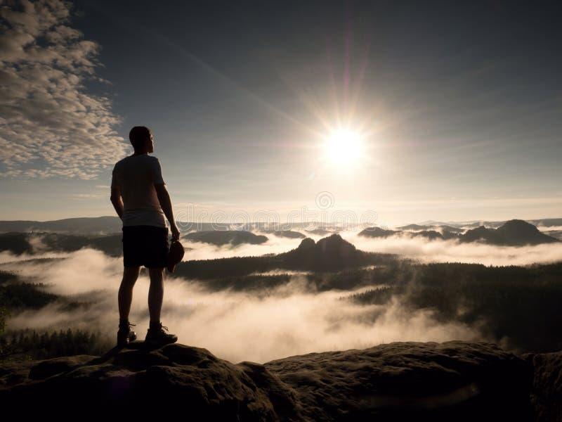 Mann an der Spitze eines Berges, der die nebelhafte Landschaft schaut Glauben Sie frei lizenzfreie stockfotografie