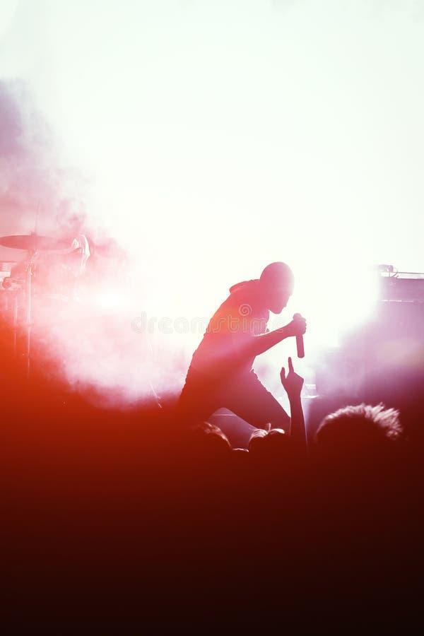 Mann an der Spitzes-Schattenbild, das der Menge auf einem Konzert auf einem Stadium zum Mikrofon singt stockbilder