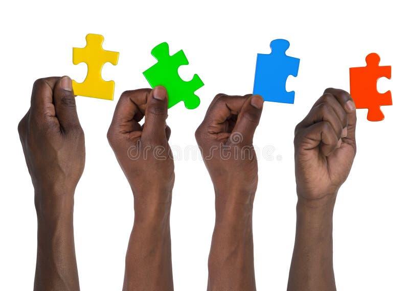Mann, der Stücke des Puzzlen hält stockbild