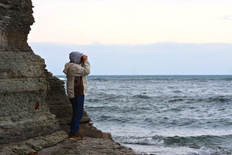 Mann, der stürmisches Meer betrachtet lizenzfreie stockfotos