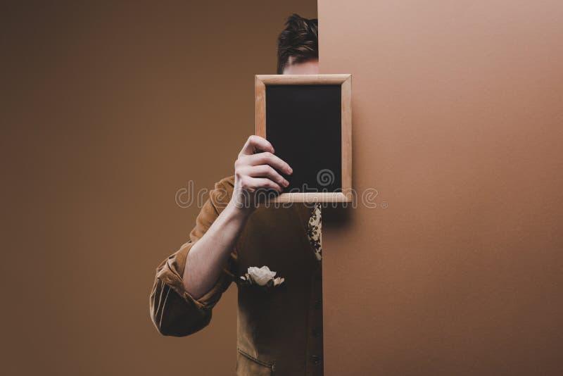 Mann in der stilvollen Kleidung, die leeren Rahmen hält stockfotografie
