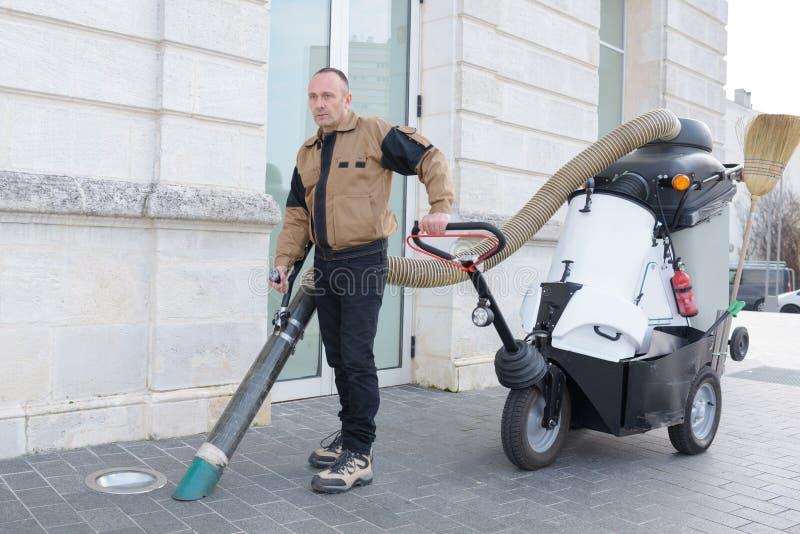 Mann, der Straßenreinigungsmaschine verwendet lizenzfreie stockfotografie