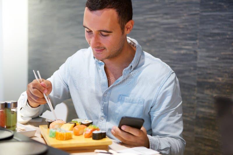 Mann, der am Sushi-Restaurant mit Mobiltelefon sitzt stockbild