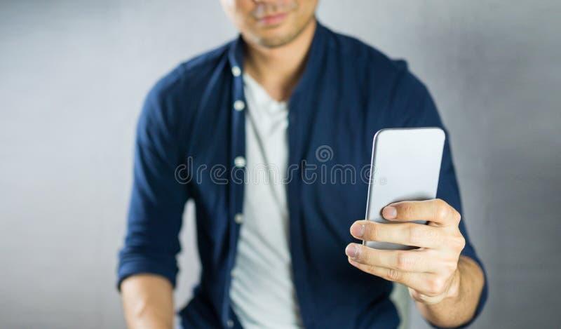 Mann, der Telefon auf grauem Hintergrund verwendet lizenzfreies stockfoto