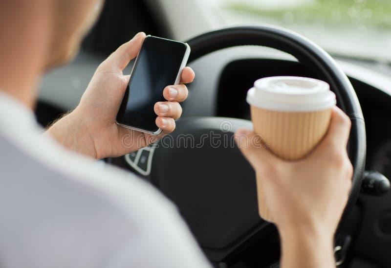 Mann, der Telefon beim Fahren des Autos verwendet stockbild