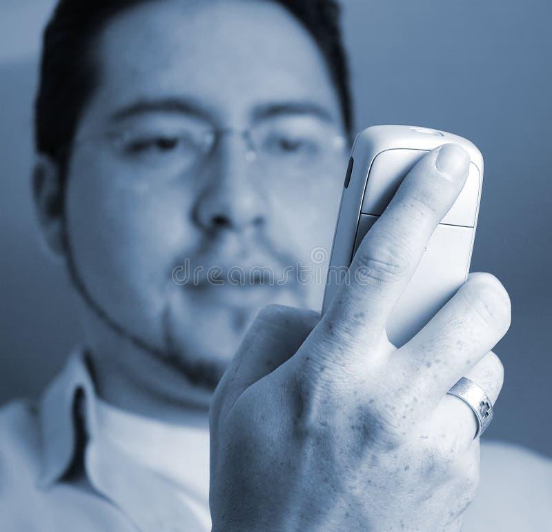 Mann, der Telefon betrachtet stockbild