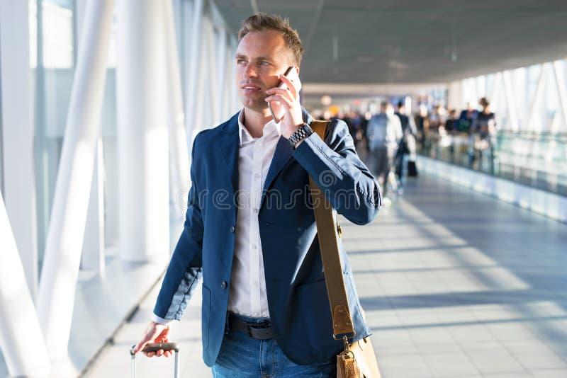 Mann, der am Telefon im Flughafen spricht
