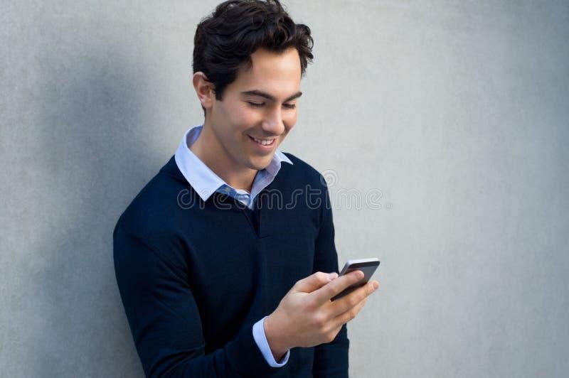 Mann, der am Telefon simst stockbild