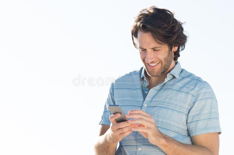 Mann, der am Telefon simst lizenzfreies stockfoto