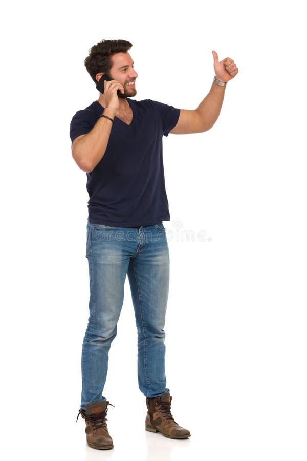 Mann, der am Telefon spricht, weg schaut und sich Daumen zeigt lizenzfreies stockbild