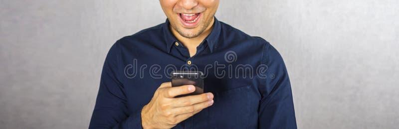 Mann, der Telefon und Lächeln auf grauem Hintergrund verwendet stockfotografie