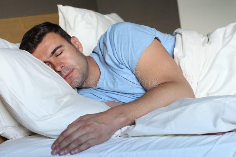 Mann, der tief im bequemen Bett schläft lizenzfreies stockbild