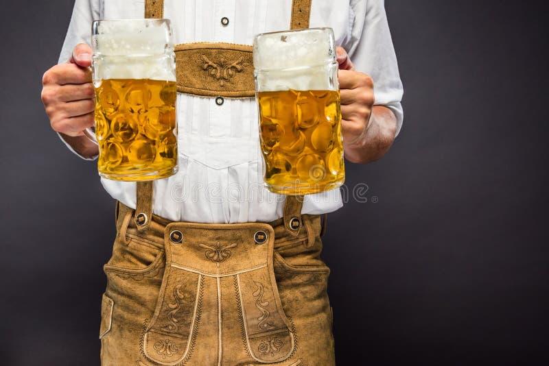 Mann in der traditionellen bayerischen Kleidung, die Becher Bier hält lizenzfreie stockfotos