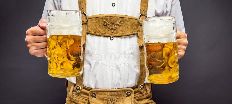 Mann in der traditionellen bayerischen Kleidung, die Becher Bier hält stockbilder