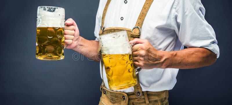 Mann in der traditionellen bayerischen Kleidung, die Becher Bier hält lizenzfreies stockbild