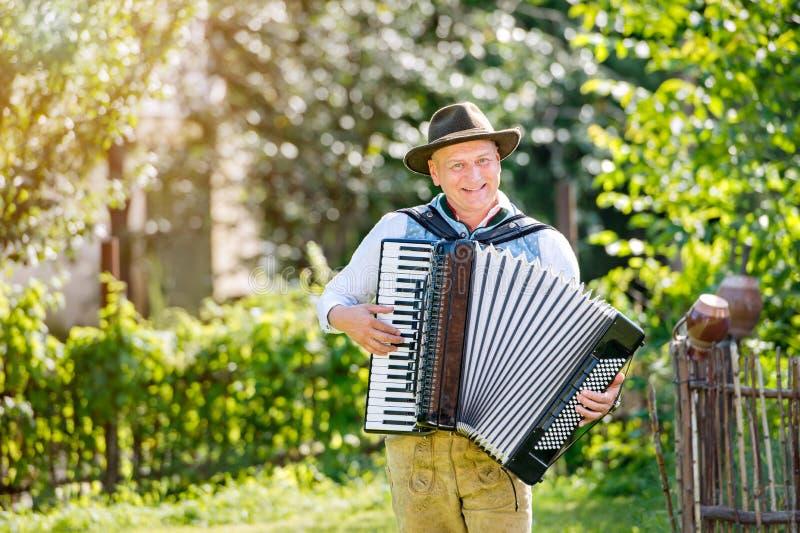 Mann in der traditionellen bayerischen Kleidung, die das Akkordeon spielt stockfotos