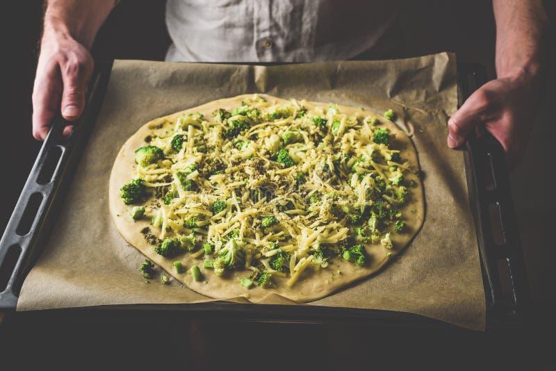 Mann, der ungekochte Pizza mit Brokkoli und Käse hält stockfoto