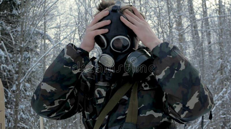 Mann in der Uniform, die eine Gasmaske im Winterwaldporträt eines jungen Soldaten trägt eine Gasmaske gegen eine Natur trägt lizenzfreies stockfoto