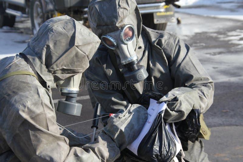 Mann in der Uniform, die eine schwarze Abfalltasche markiert lizenzfreies stockbild