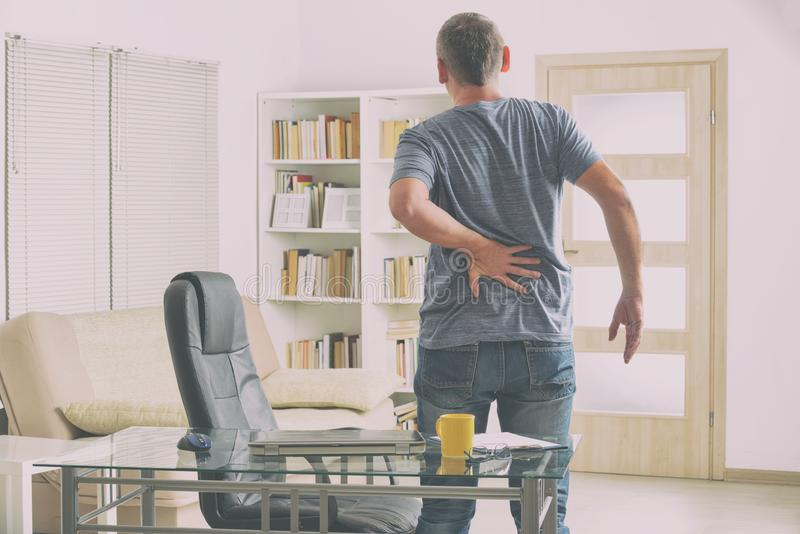 Mann, der unter Rückenschmerzen leidet stockfotografie
