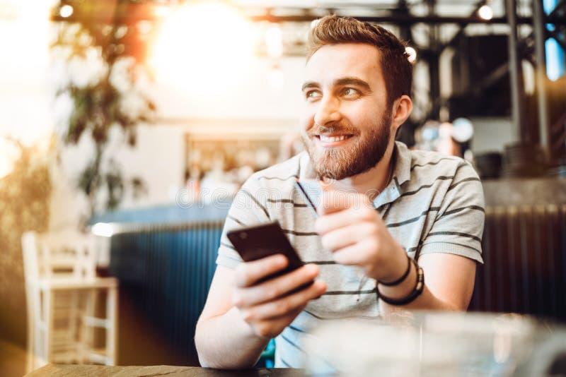 Mann, der unter Verwendung der Kreditkarte und des Handys zahlt Modernes Zahlungssystemkonzept lizenzfreies stockfoto