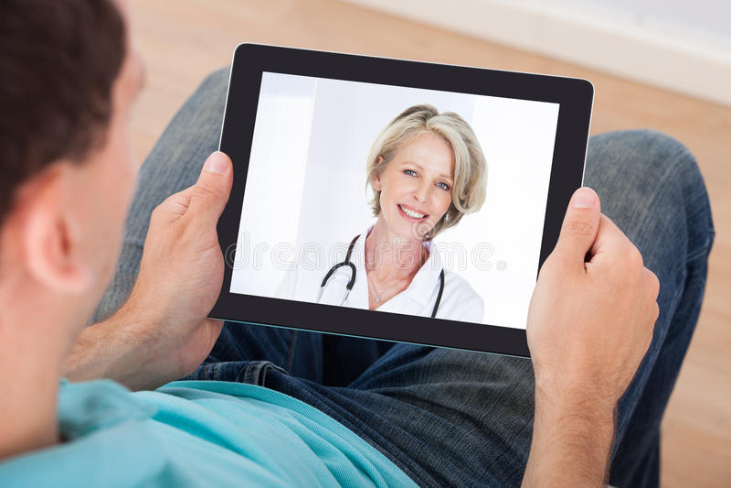 Mann, der Videochat mit Ärztin hat lizenzfreies stockbild