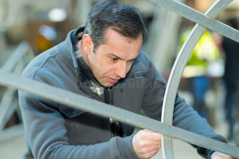 Mann, der Vollenden in der Fabrik kontrolliert stockbilder