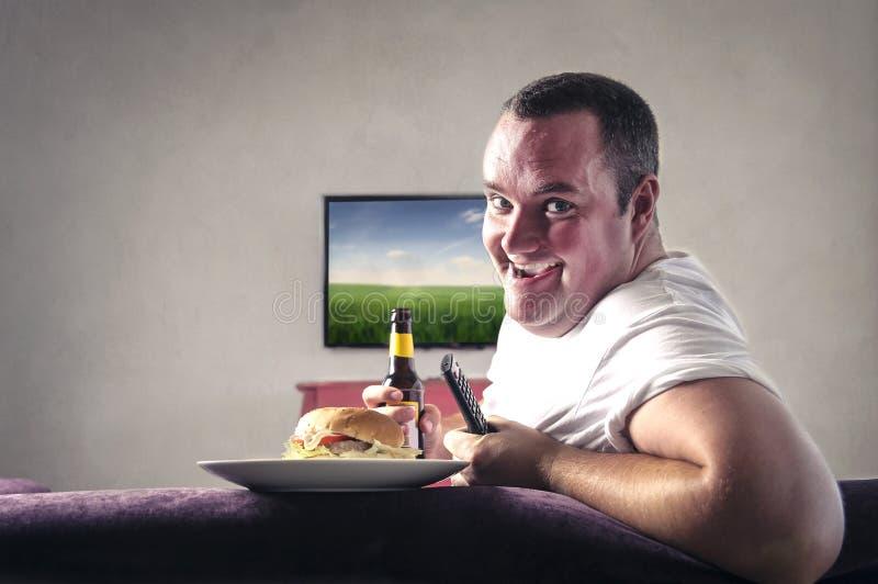 Mann, der vor dem Fernsehen trinkt und isst lizenzfreies stockbild
