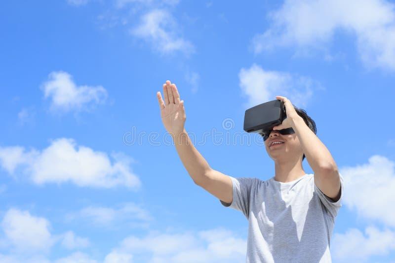 Mann, der VR-Kopfhörergläser verwendet stockfotografie